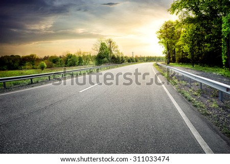 Asphalt road leaving for turn to the sun under a dramatic sky