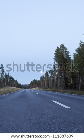 Asphalt road nighttime with clear sky and moon, Dalarna, Sweden - stock photo