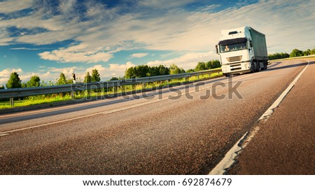 asphalt road on dandelion field with a small truck. lorry moving on sunny evening