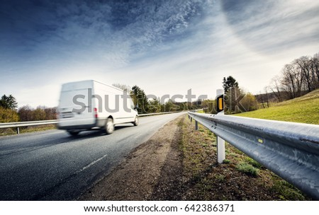 asphalt road on dandelion field with a small truck. van moving on sunny day #642386371