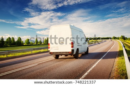 asphalt road on dandelion field with a small truck. van moving on sunny day #748221337
