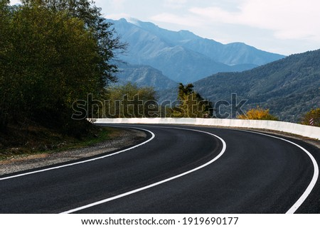 Asphalt road. Paved road on the background of mountains. Road on the background of beautiful mountains in the Caucasus. Landscapes of the country. Journey through beautiful places by car. Copy space
