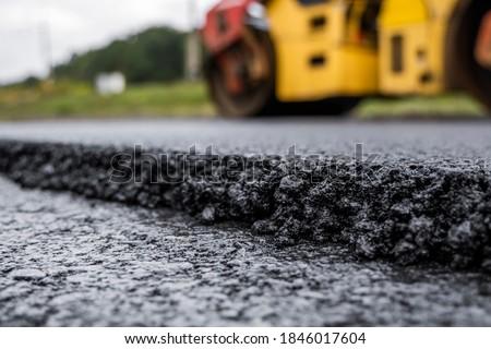 Asphalt road roller with heavy vibration roller compactor press new hot asphalt on the roadway on a road construction site. Heavy Vibration roller at asphalt pavement working. Repairing.
