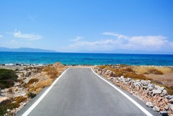 Asphalt road that ends in the sea. Concepts of beginning, relaxation, harmony