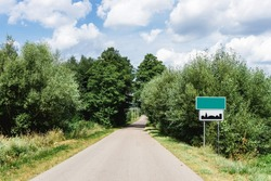 Asphalt road through the forest. Summer coniferous forest travel landscape. Long empty straight road and blue cloudy sky above. Empty copy space blank city name sign. Build up area road sign.