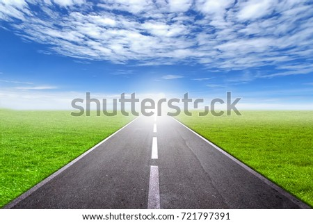 asphalt road through the green...