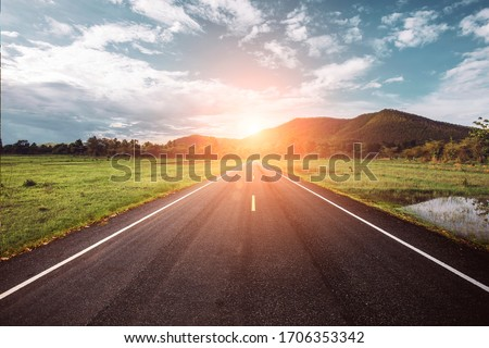 Asphalt road through the green field and clouds on blue sky in summer day. Beautiful grassland road in Thailand.Highland road. Сток-фото ©