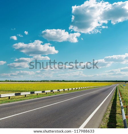asphalt road under cloudy sky - stock photo