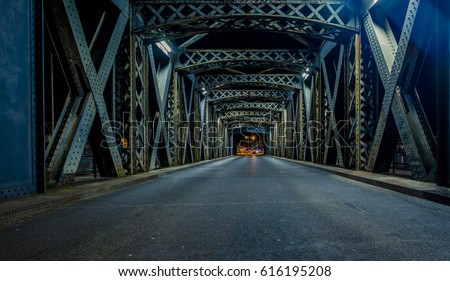 Asphalt road under the steel construction of the illuminated bridge in the city. Night urban scene with car light trails in the tunnel. Citylife, transport and traffic concept. Toned #616195208