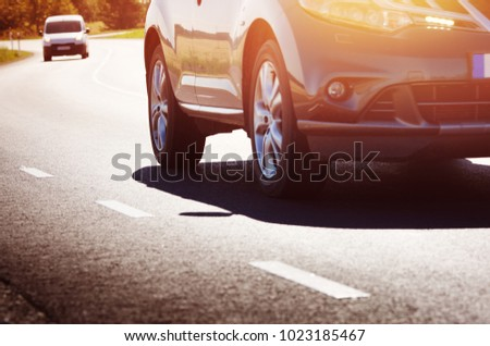 asphalt road view with a car in countryside at beautiful sunset #1023185467