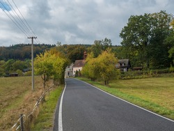 Asphalt road winding in small village Travnik with chapel , country house and cottage in autumn colorful landscape, moody sky. Luzicke hory Lusatian Mountains, Czech Republic.
