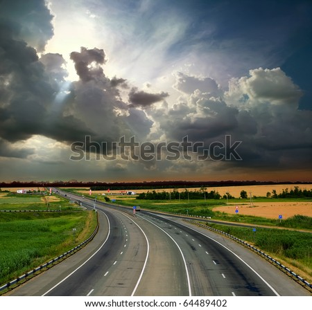 Asphalt road with a fence against the blue sky