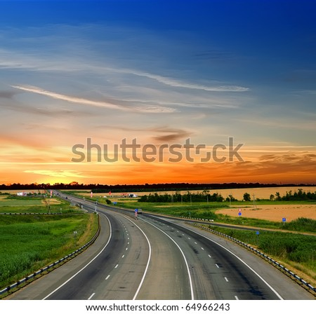 Asphalt road with a fence against the blue sky