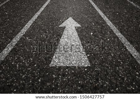 Asphalt road with an arrow pointing forward on the surface. An image of a milestone roadmap is a representation of success in the future goal #1506427757