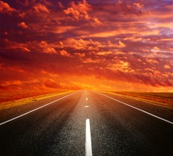 Asphalt road with light on a horizon and clouds