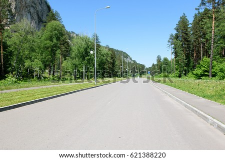 Asphalt road with sidewalks and streetlights on a sunny summer day in the forest. In Altai region.