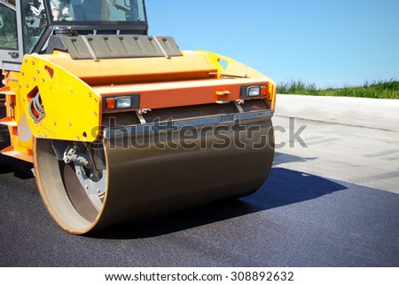 Asphalt roller at work, construction of new roads, repair of pavement, lining country roads, modern construction equipment