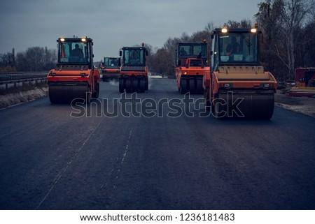 Asphalt rollers rolling new hot asphalt at dusk. Road construction. #1236181483