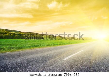 Asphalt rural road to sunrise