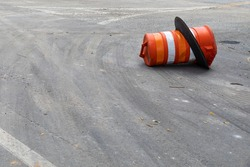 Asphalt street surface with orange traffic barrel on its side, safety and road hazard, copy space, horizontal aspect
