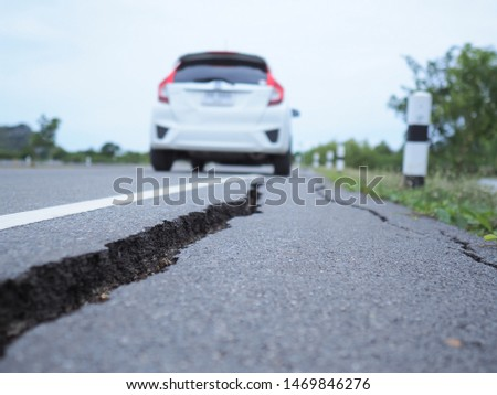 Asphalt surface on the street was demolished due to poor construction,traveling by car on dangerous roads,cracked road after earthquake