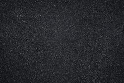 Asphalt texture, black pattern of roadway, grainy surface of pavement. Abstract dark wallpaper.