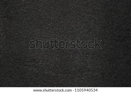 Asphalt with fine grain texture. Close-up of black road background. Top view of the rough surface