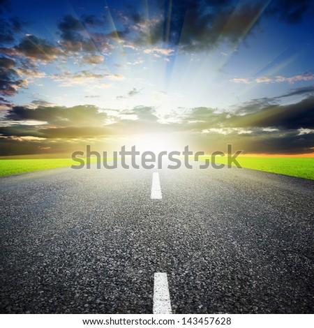 Asphalted highway over sunset sky background