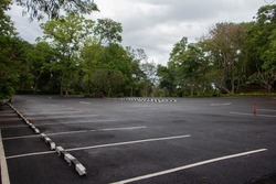 Asphaltic parking lot surrounded by forest. No car are parked.