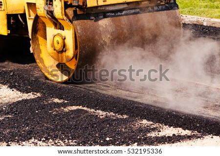 asphalting of the road with steamroller stock photo