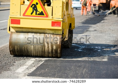 Asphalting paving repairing works with vibrator compactor machine during Road street