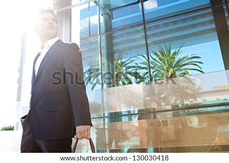Aspirational fashionable businessman in the city with a reflective modern office building in the background and the sun filtering through his face.