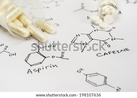Aspirin in capsules and caffeine in tablets on paper with their chemical formula
