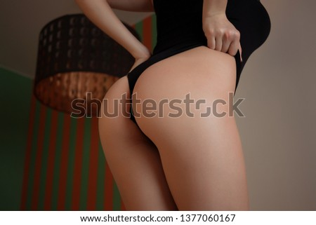 Ass of sensual woman in lingerie in room