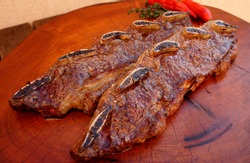 Assado de Tira or Strip roast. Traditional beef rib cut for a delicious barbecue on wooden background