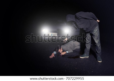 Assassin shooting man in suit in front of car on route with silence pistol  #707229955