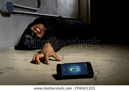 Assaulted gangster calling for help or medical emergency with a cell phone. On the foreground is a cell phone he was using to call 911.  He is laying on the ground injured.
