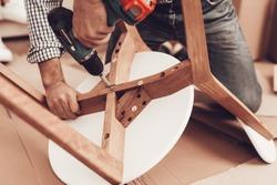 Assemble Furniture. Man Repairing Chair. Man Collects Chair. Furniture Assembler with Drill. Woman on Sofa with Laptop. Bright Interior. Craftsman with Tools Repairs Chair. Furniture Repair.