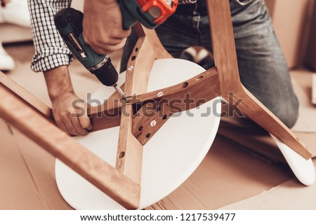 Assemble Furniture. Man Repairing Chair. Man Collects Chair. Furniture Assembler with Drill. Woman on Sofa with Laptop. Bright Interior. Craftsman with Tools Repairs Chair. Furniture Repair.