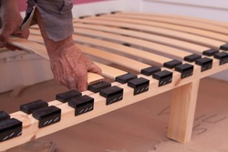 assemble the bed, senior man's hands make up wooden slats for the bed, orthopedic wooden slats for the bed