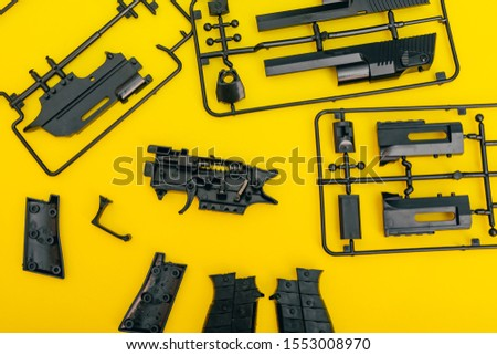 assemble toy handgun with bulllets from the parts concept on yellow background. Plastic model part kits  from top view. #1553008970