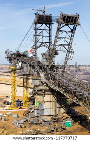 Assembling a huge coal mining excavator in a coal mine pit - stock photo
