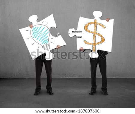 Assembling puzzles with bulb and money drawings concrete background