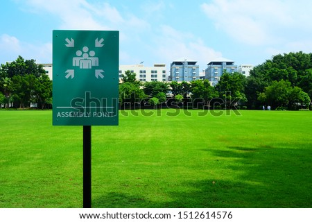 Assembly Point Sign with Green Grass Field Background. #1512614576