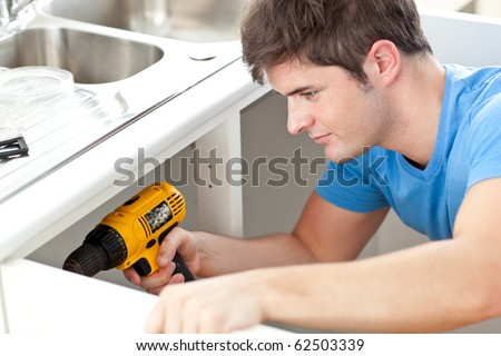 Assertive man holding a drill repairing a kitchen sink at home