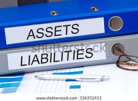 Assets and Liabilities - two binders on desk in the office #336352415