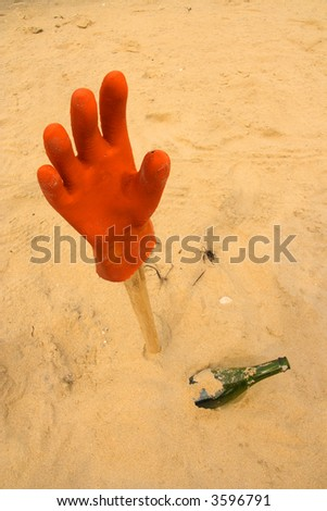 Assistance needed, hanging glove and bottle in the sand