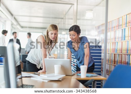 Assistant and partner coffee meeting. Focus on two women in her 30s and 40s who are standing in front of a laptop and two white coffee cup, in a luminous open space looking at balance sheets