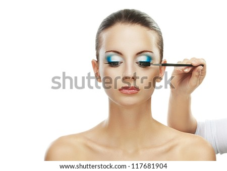 Assistant paint eyes of beautiful young woman close up, isolated on white background.