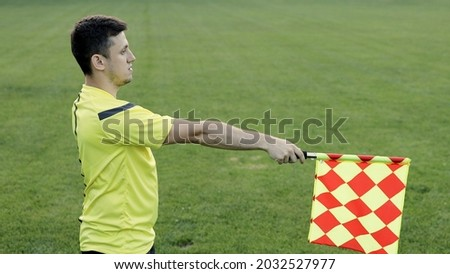 Assistant referee moving along the sideline during a soccer match. Linesman hand with flag signalling for offside trap to referee during football match